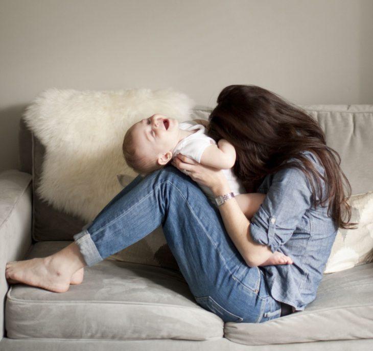 Chica mordiendo la panza de un bebé para hacerlo reír
