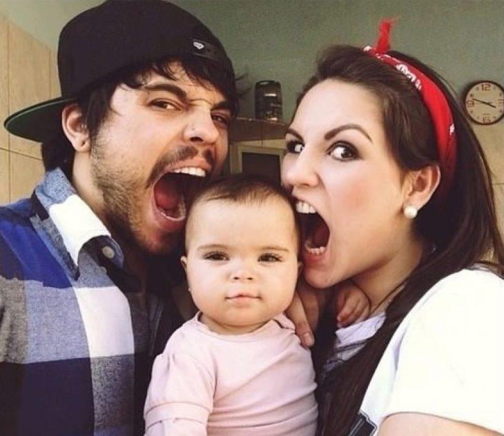 Pareja de novios intentando morder a un bebé tiernamente