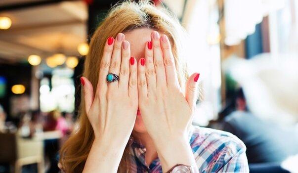 mujer con manos tapandose la cara