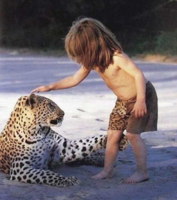 niña tipi pone su mano en la cabeza de leopardo