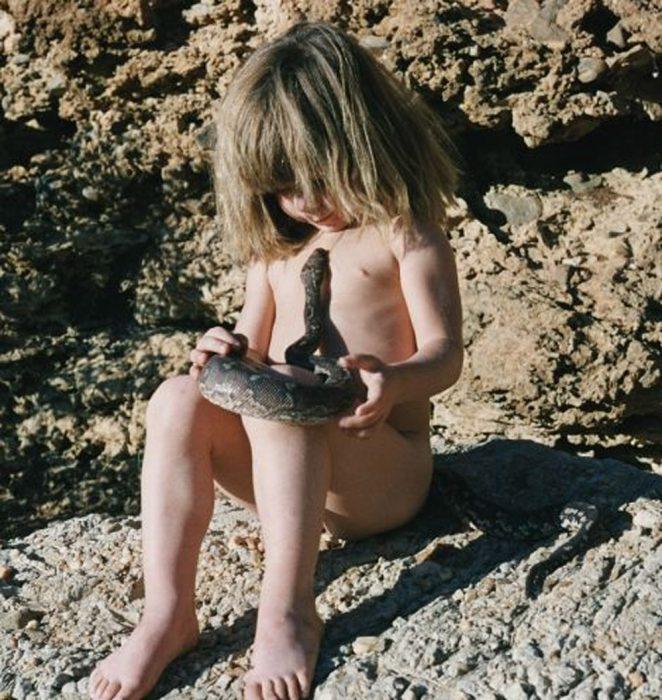 niña tippi sentada jugando con una serpiente