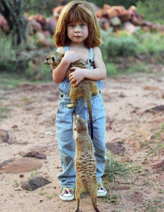 niña tippi abrazada de animales selva