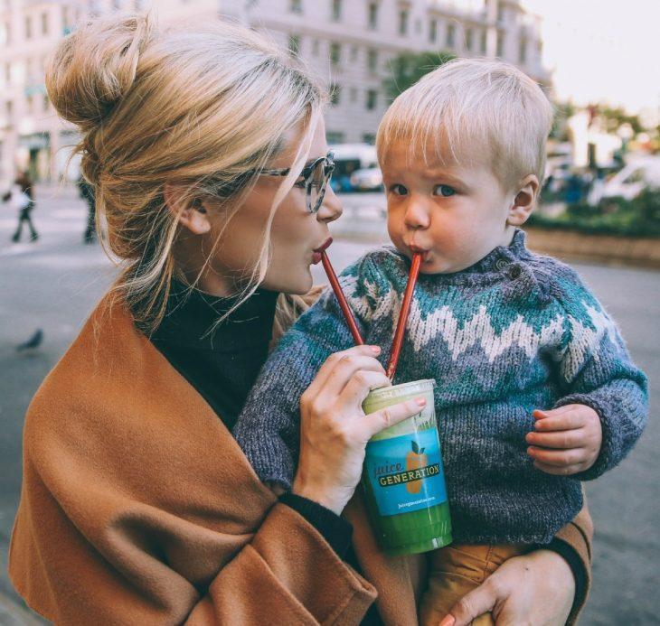 madre cargando hijo con vaso popote ciudad