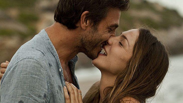 pareja de frente dandose un beso feliz