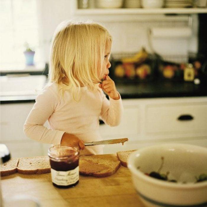niña comiendo pan y nutella en la cocina