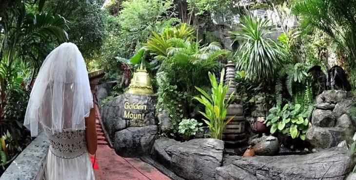 mujer con vestido de novia resando en la montaña dorada Tailandia