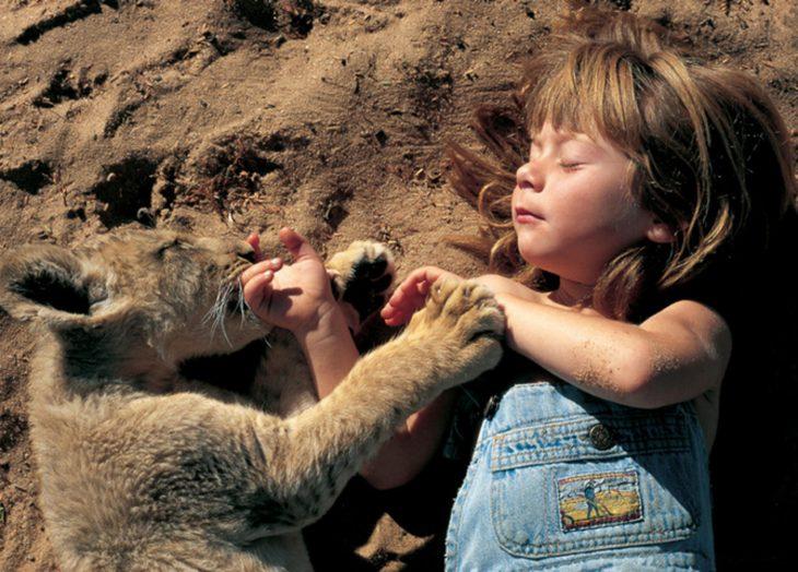 niña tippi en la arena abrazada de un leon cachorro