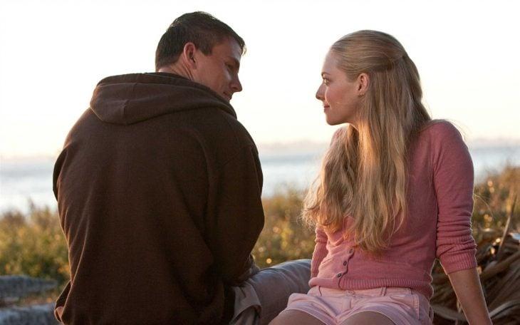 Hombre y mujer sentados en la playa se miran de frente sonriendo