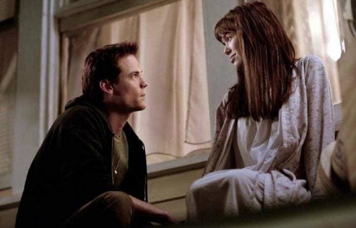 pareja sentados en una ventana enamorados