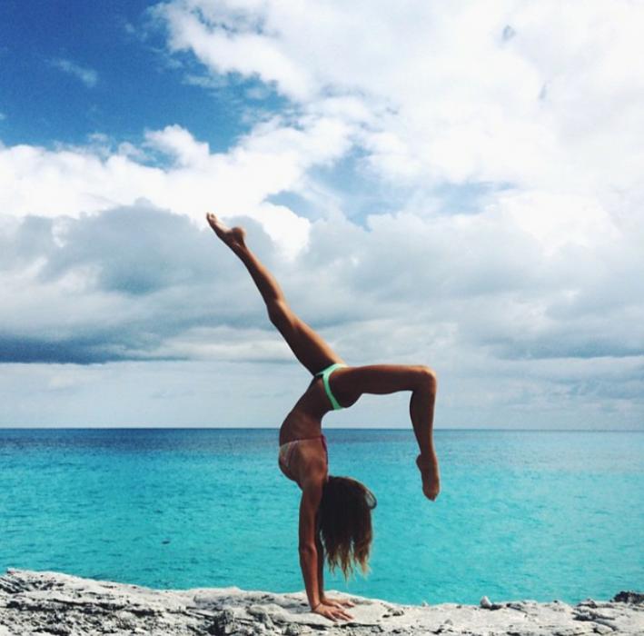 mujer en la playa haciendo yoga y acrobacia