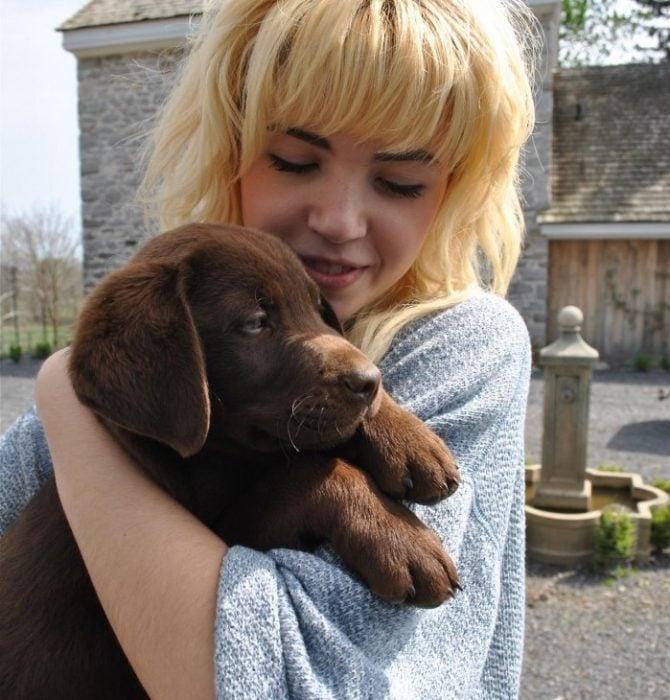 chica rubia abrazando a cachorro labrador cafe
