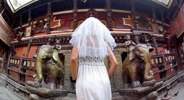 Mujer con vestido de novia en la puerta de oro en kathmandu Nepal