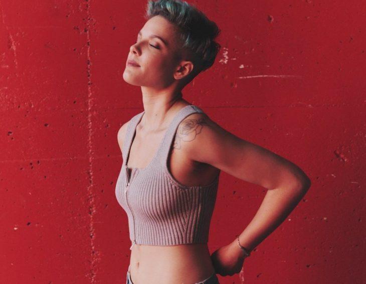 chica con jeans y top cabello corto pared rojo