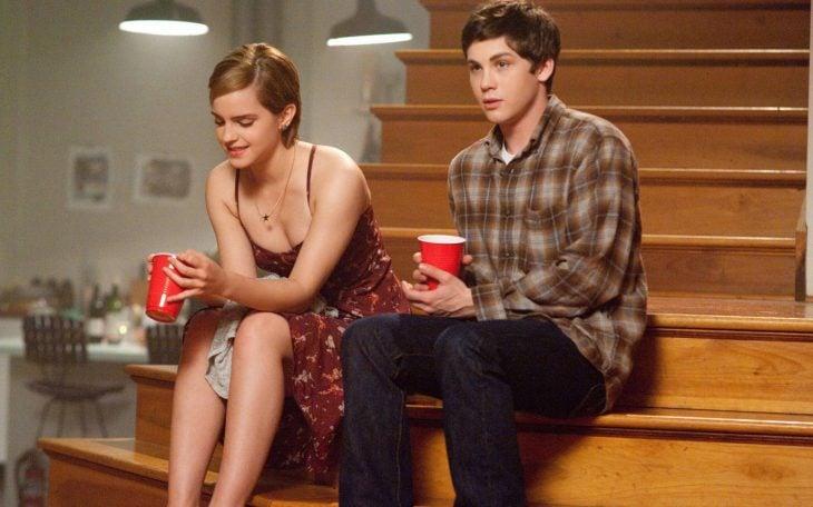 chica y chico sentados en las escaleras con bebida fiesta