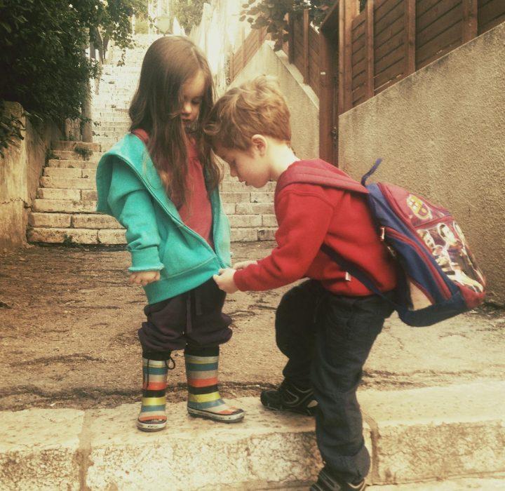niño le ayuda a su hermana a abrocharse la sudadera