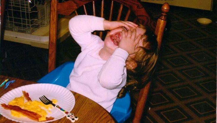 niña sentada en la mesa haciendo rabieta berrinche