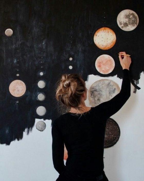 mujer pintando en la pared galaxia y planetas artista
