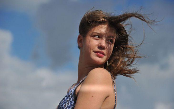 chica linda sonrie con cabello volando en el viento