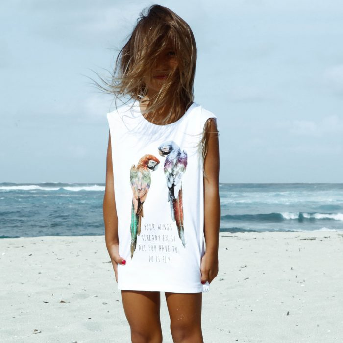 niña playera de guacamayas en la playa