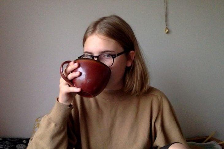 chica sentada tomando cafe en taza grande rubia