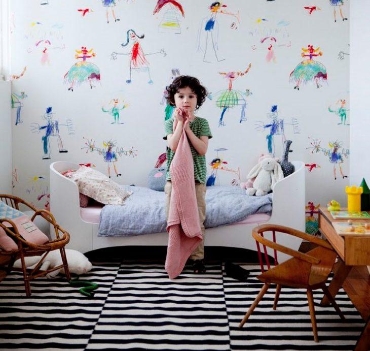 niño de pie en su cuarto con una cobija