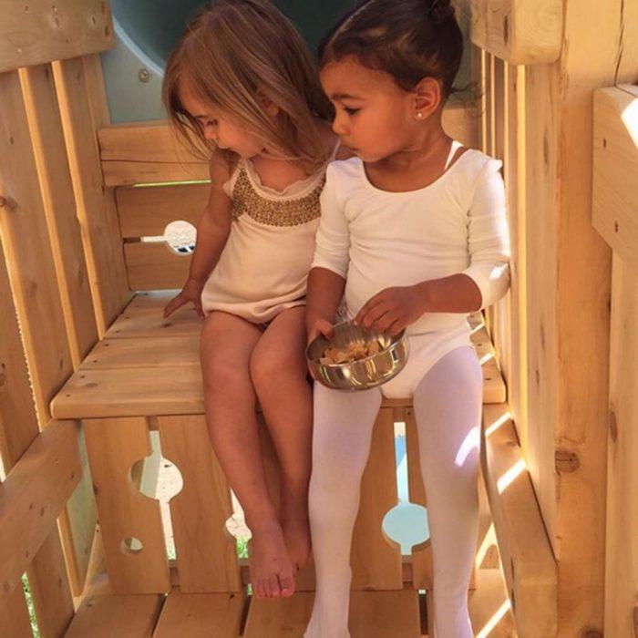 dos niñas sentadas en casa de madera primas