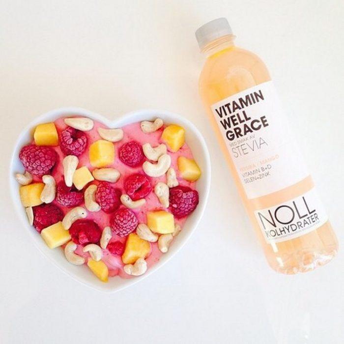 plato de frutas en forma de corazon y agua con vitaminas