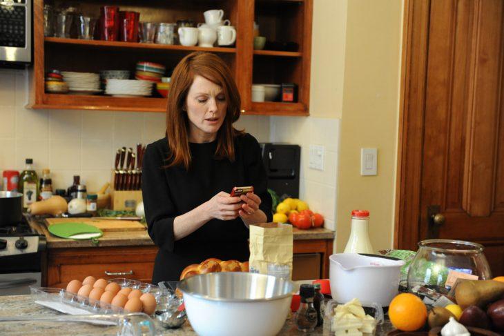 mujer pelirroja en la cocina viendo su celular