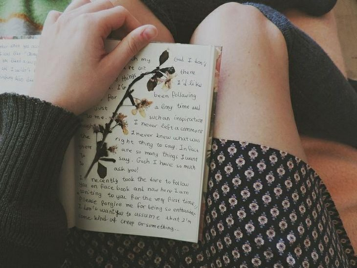 una libreta de apuntes y rodillas de chica en falda