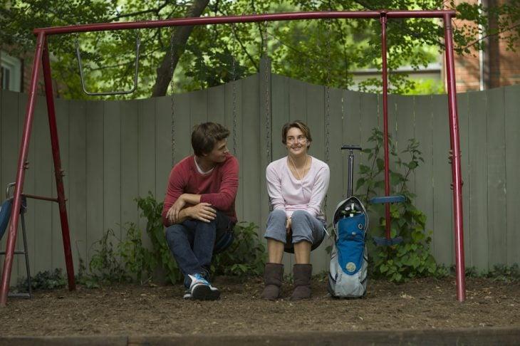 chico y chica sentados en un columpio platicando sonríen