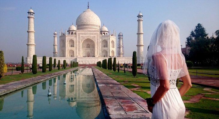 mujer con vestido de novia frente el taj mahal en la inda