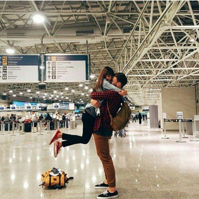 pareja en aeropuerto besandose flores en el suelo