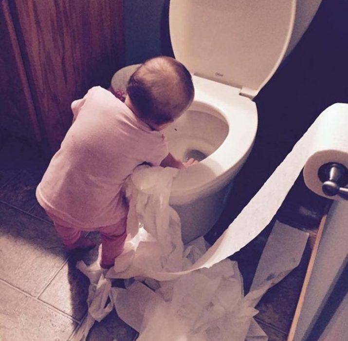 niña jugando con el papel de baño y el retrete