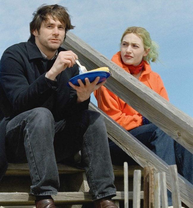 pareja sentada en unas escaleras hombre comiendo y platicando