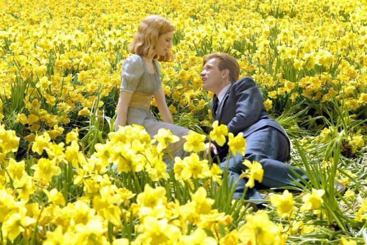 hombre y mujer sentados en un campo de flores amarillas