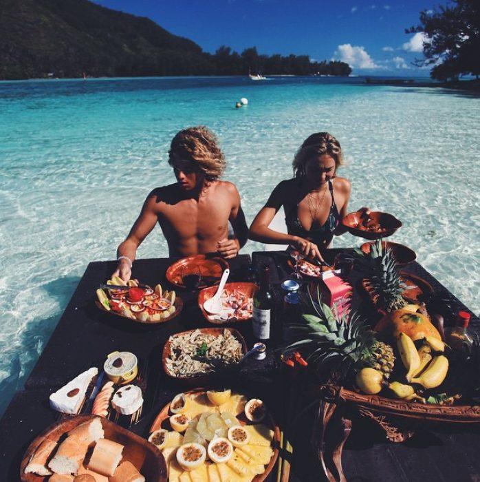 pareja comiendo frutas en la playa