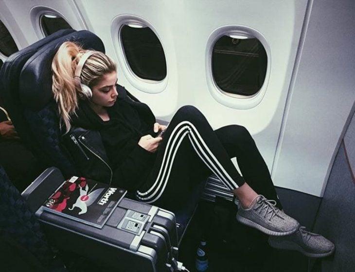 chica acostada en el asiento de avion escuchando musica viaje