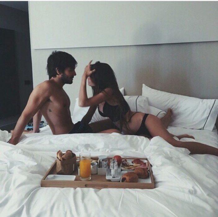 pareja en la cama comiendo desayuno en ropa interior