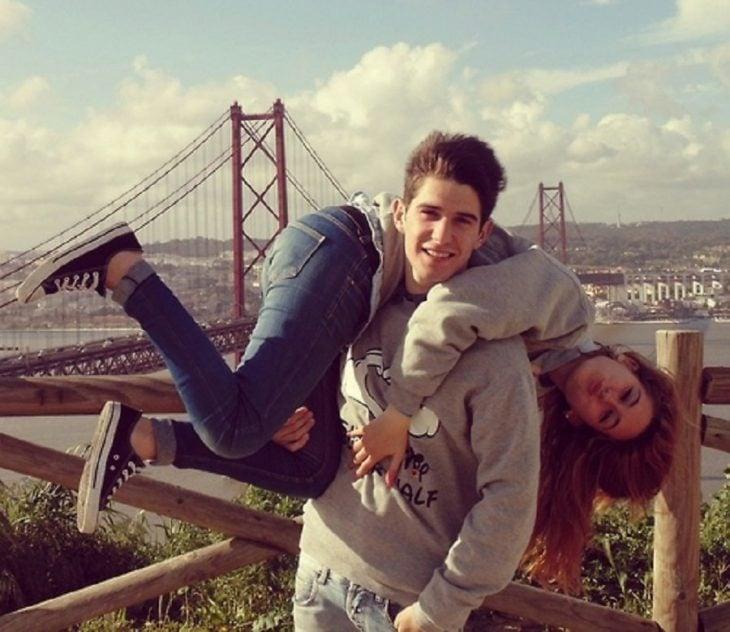 chico cargando a su novia con puente atras paisaje