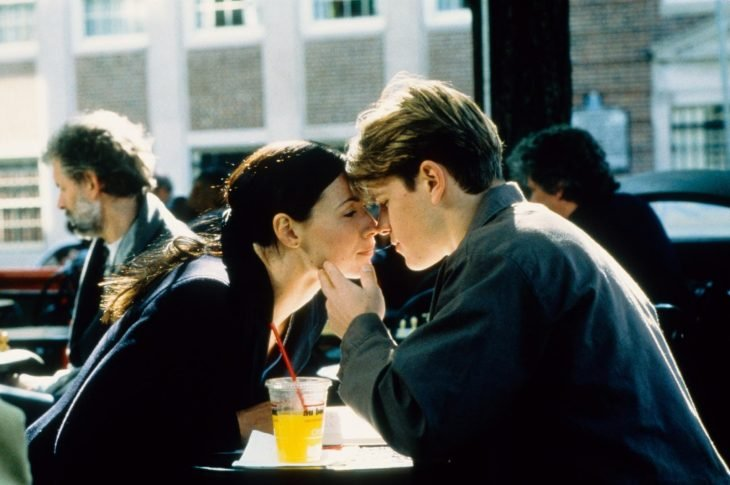 pareja en una mesa de restaurante se acercan para besarse