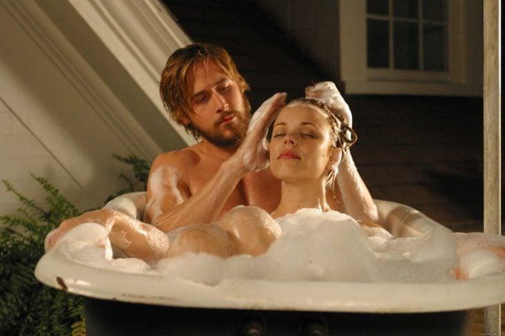 pareja dentro de bañera y espuma lava su cabello