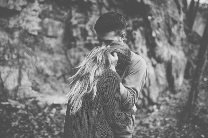 Pareja abrazada en medio de un bosque