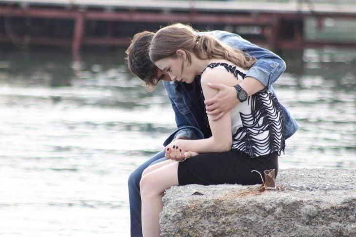 Pareja abrazada platicando en la orilla de un lago