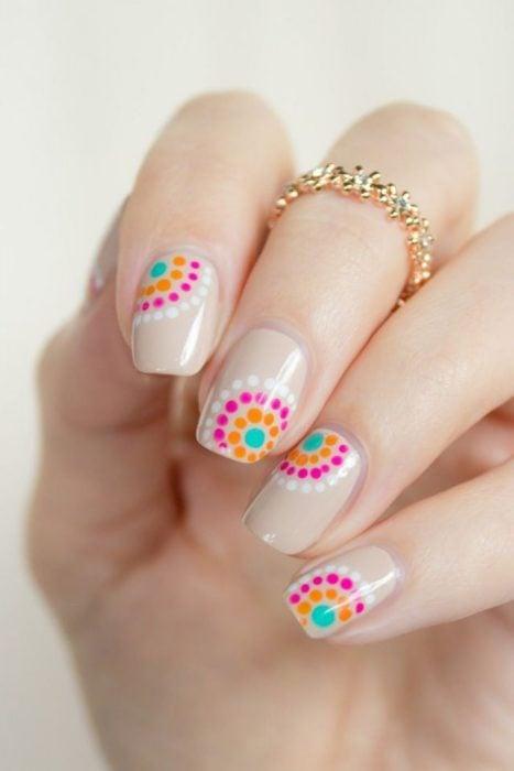 Ногти оформлены в обнаженном цвете с розовыми и оранжевыми точками