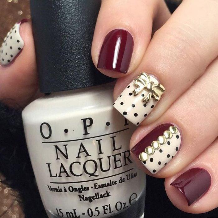 Ногти украшены сливовым и белым цветом с черными и золотистыми точками