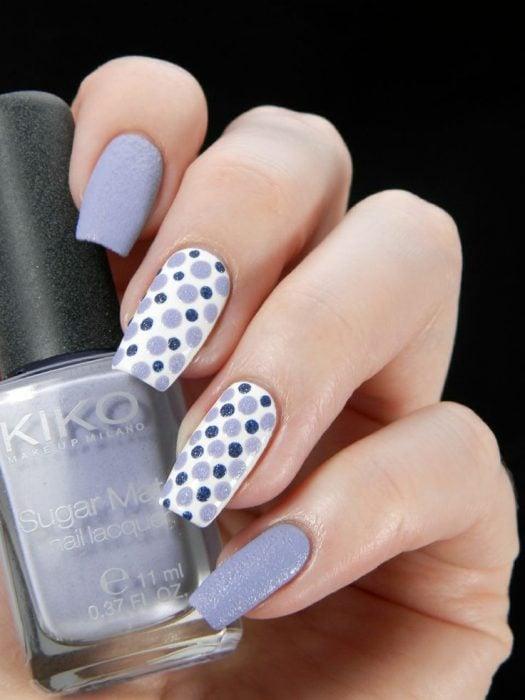 Ногти оформлены в фиолетовом цвете с белыми и синими точками
