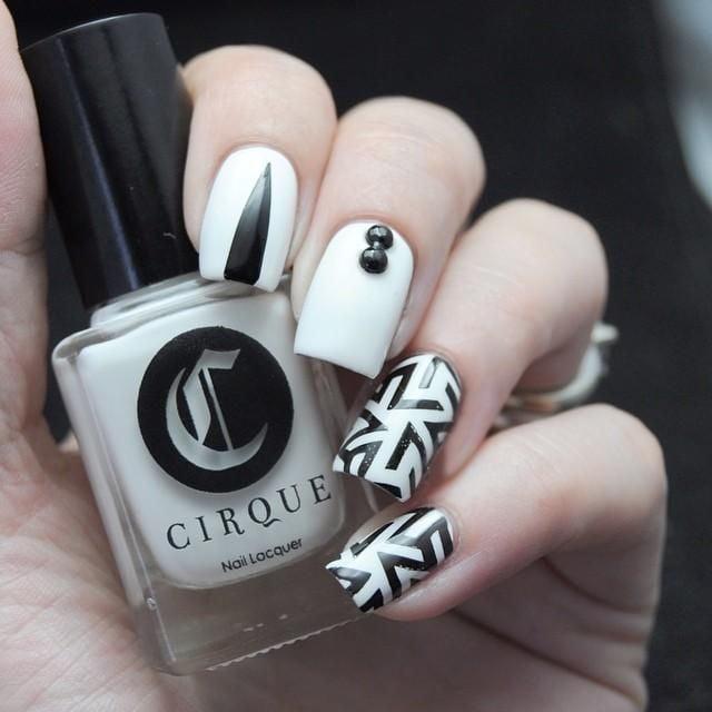Uñas decoradas en color blanco con lineas negras