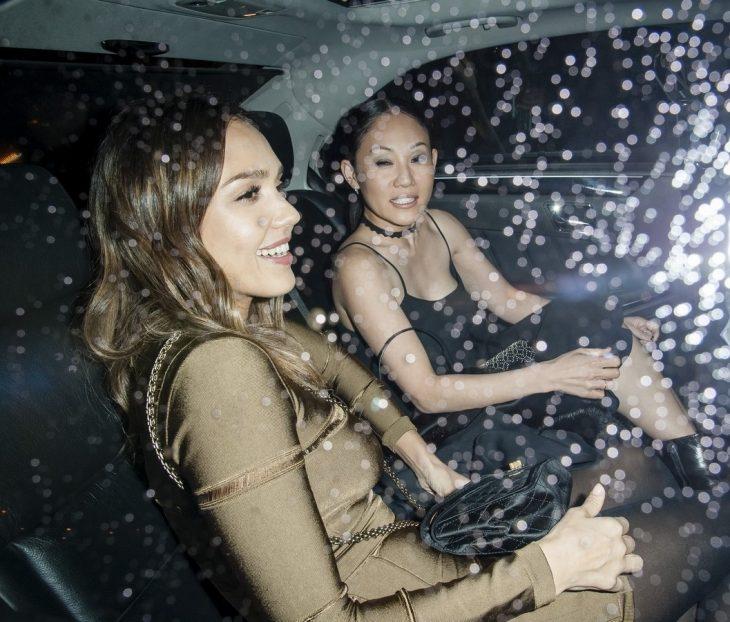 mujeres dentro de un coche con vidrio arriba de noche