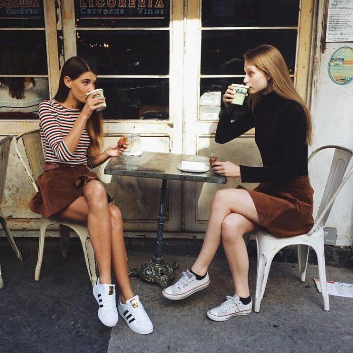 dos mujeres de frente tomando un café