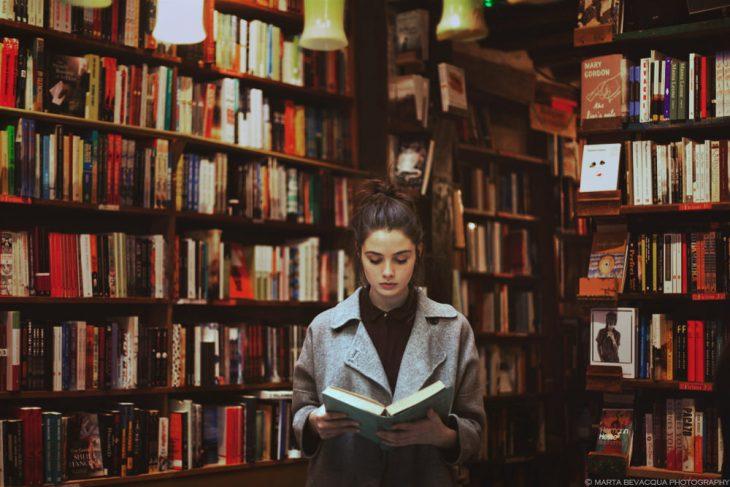 Chica leyendo un libro en una biblioteca
